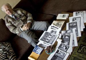 Wilhelm Brasse mirando sus fotos